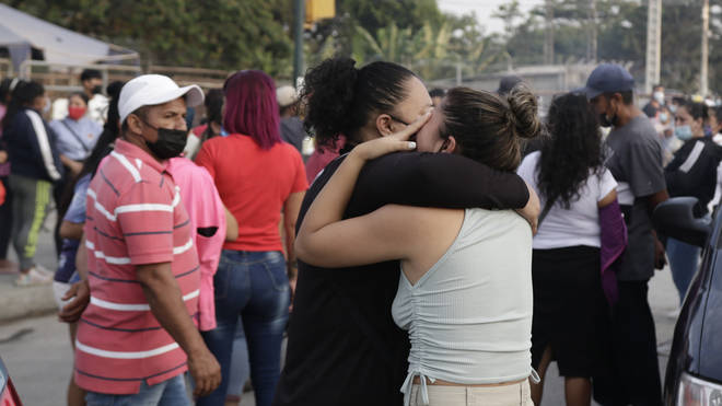 Women wait for information about relatives who are inmates at Litoral prison in Ecuador following the violence