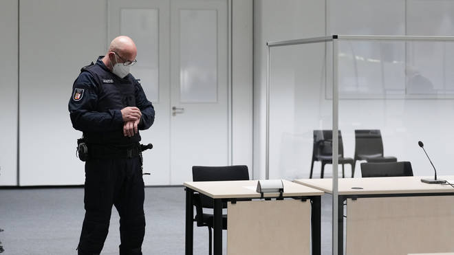A judicial officer at the court room in Itzehoe, Germany, looks at his watch prior to the trial