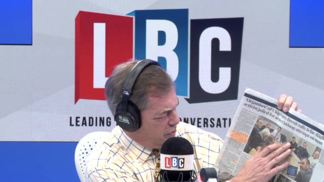 Nigel Farage points to a photograph of Tommy Robinson at a Ukip meeting in the newspaper.