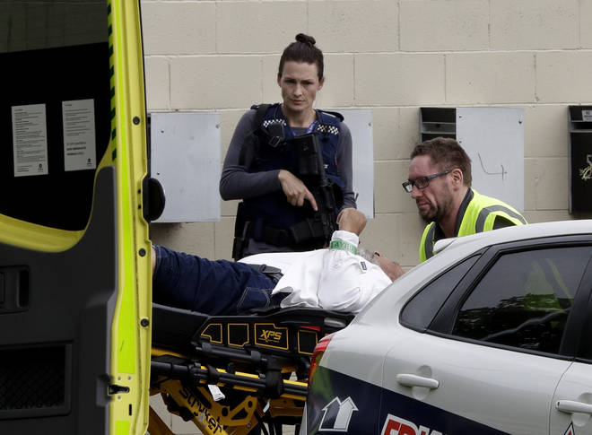 Armed police watch as a man is taken to hospital after the Mosque shooting in New Zealand