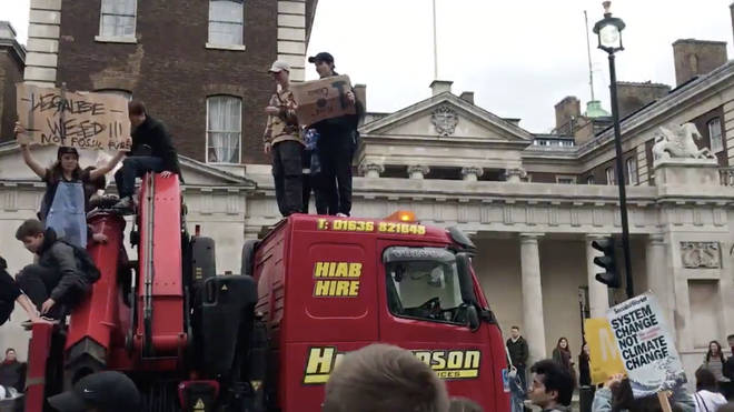 The moment students on strike climb onto the roof of a lorry which became stuck in climate change protests in central London