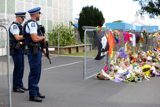 Two police officers stand near tributes to the victims of a shooting in Christchurch, New Zealand