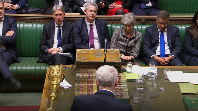 Theresa May listens to Jeremy Corbyn's speech