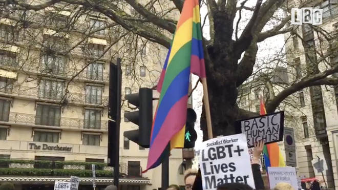 An LGBT flag is waved by protesters outside the Dorchester Hotel