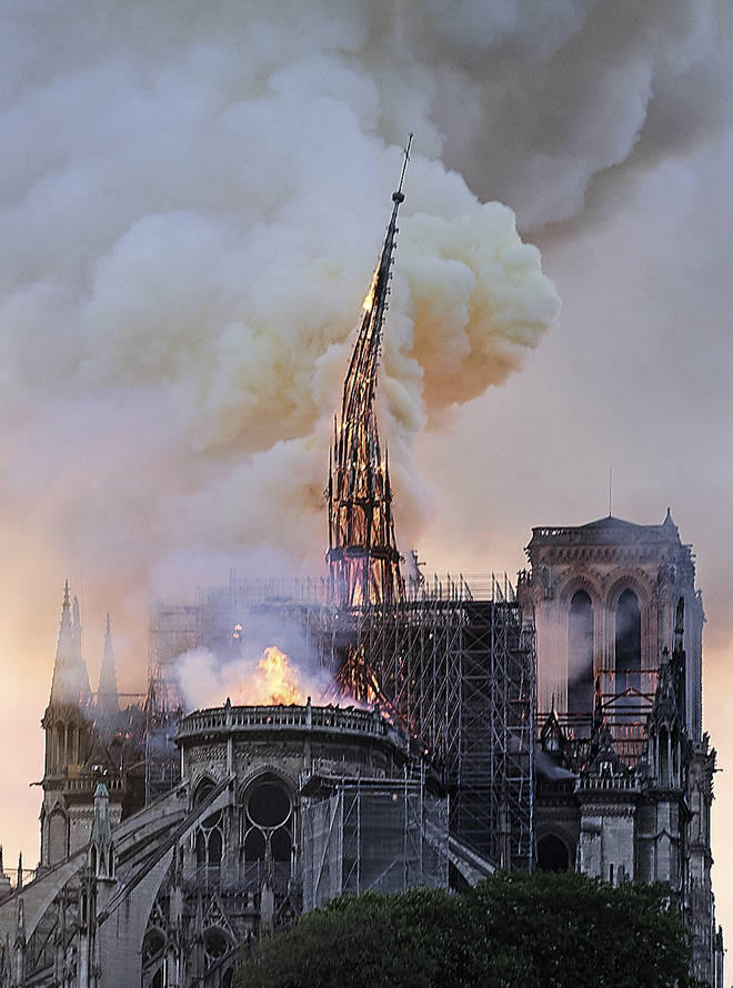 Flames and smoke rise as the spire on Notre Dame cathedral collapses in Paris