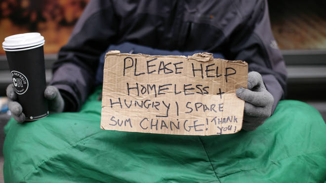 A homeless man asks for spare change