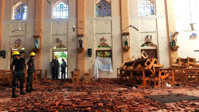 Investigators amongst the debris after an explosion at St Sebastian's Church in Negombo, Sri Lanka