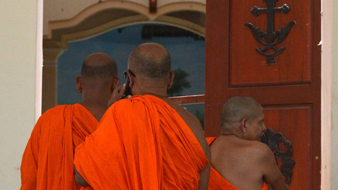 Sri Lankan Buddhist monks visit the site of a bomb attack at St. Sebastian's Church in Negombo