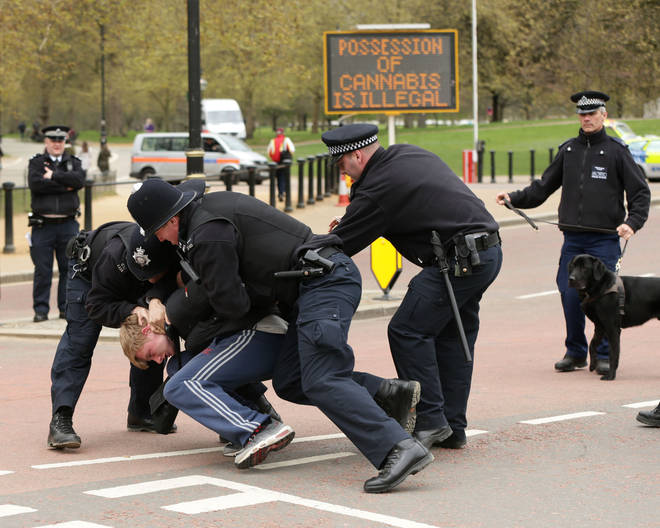 Police restrain a man at an entrance to Hyde Park, central London, during a '420 Celebration' pro-cannabis event