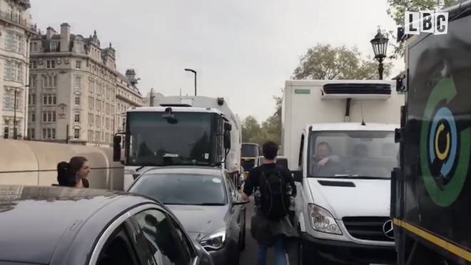 The lorry driver points to the tailback behind him as he rants to a campaigner over the disruptions facing Londoners