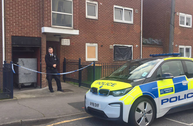 A police officer guards the address in Canning Town.