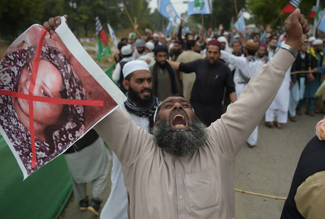 A supporter of the Ahle Sunnat Wal Jamaat (ASWJ), a hardline religious party, holds an image of Christian woman Asia Bibi during a protest rally.
