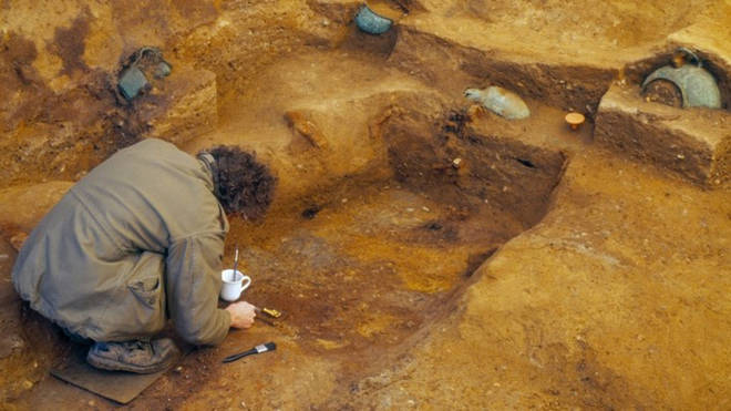 Archaeologists examine the tomb.