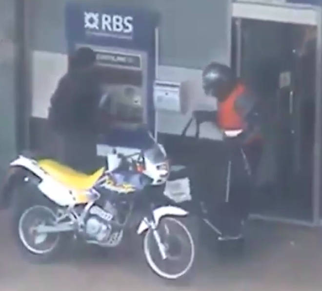 One of the suspects leaves the bank.