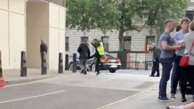 The shocking moment a homeless man is kicked in the back by a security guard in Westminster
