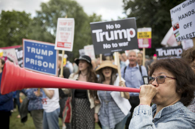 A woman blows a vuvuzela at a Trump protest at Buckingham Palace
