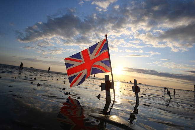 Crosses of remembrance placed alongside a Union flag stand at dawn on the beach at Arromanches in Normandy, northern France, ahead of a day of events to mark the 75 anniversary of D-Day.