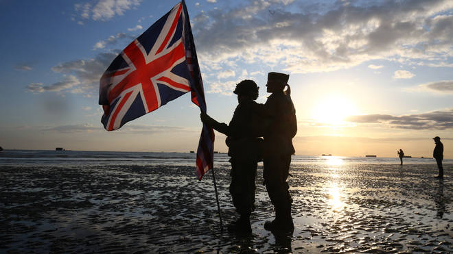Military reenactors carrying the British flag
