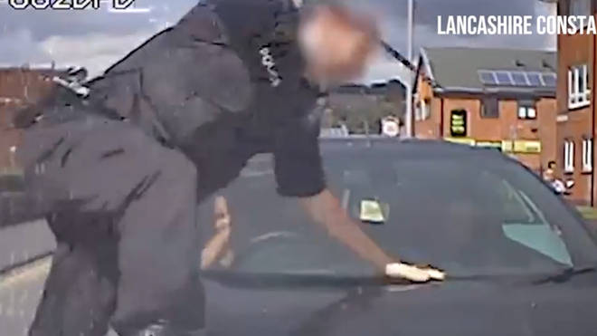 One officer vaults over the car after smashing one window.