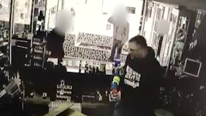 Shopkeeper uses water gun to defend shop.