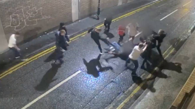 Shocking images released by police show one lout kicking a man as he lays on the floor.