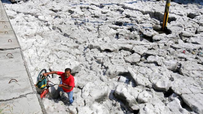 A man with a bike walks on hail in Guadalajara