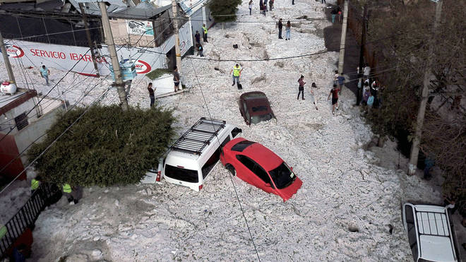 Vehicles buried in hail are seen in the streets of Guadalajara