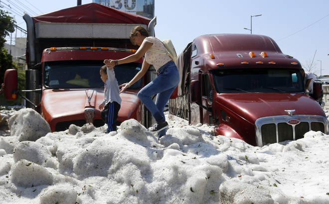 A woman and child walked across a metre-high layer of ice after a freak hailstorm in Mexico