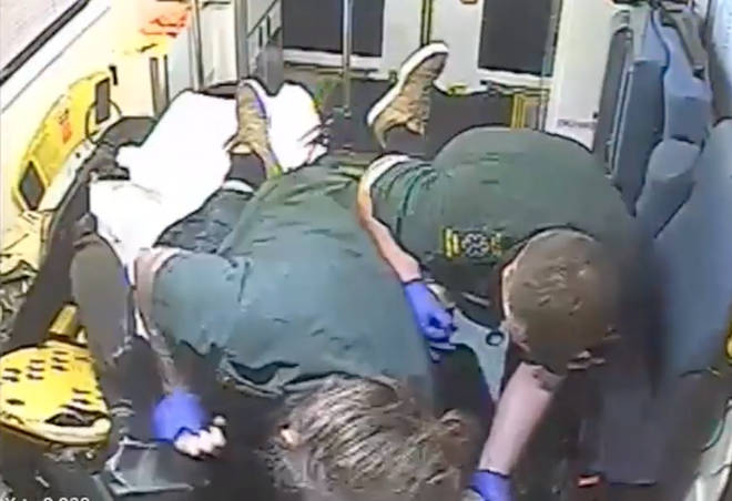 The two ambulance workers struggle to restrain the violent man.
