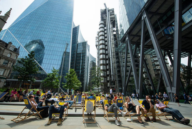 People sit on deckchairs near the Lloyds of London building, London, as more hot weather is due to hit the UK this week.