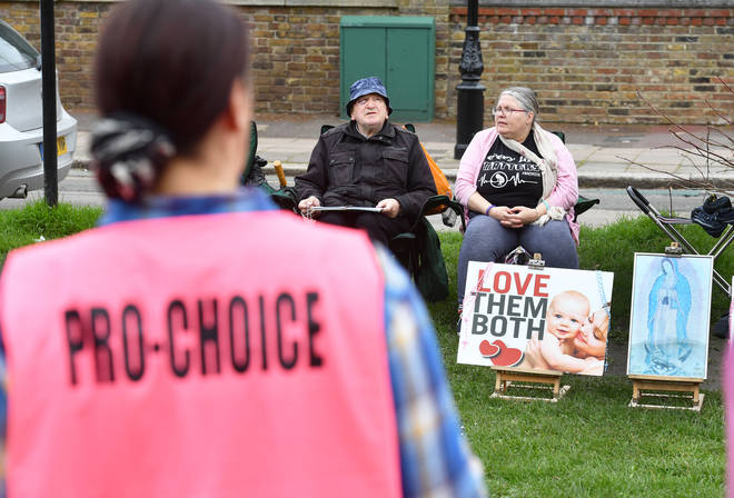Pro-choice activist stands opposite anti-abortion protesters in Ealing, west London