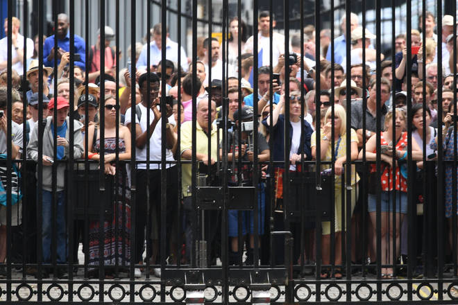 A crowd waits at the end of the street waiting for outgoing Prime Minister Theresa May to leave 10 Downing Street