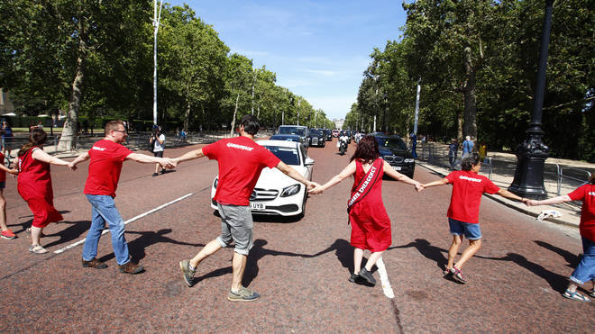 "Greenpeace activists wearing sashes reading ""Climate Emergency"" held hands to form a human chain across The Mall stalling the incoming Prime Minister's journey to meet the Queen."
