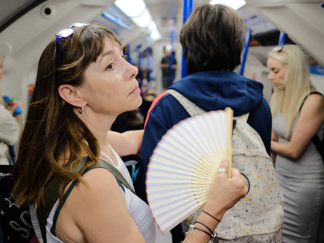 A woman uses a fan to cool down on a tube train in central London as the UK is expected to edge towards its hottest ever July day, with the mercury due to soar above 30C (86F).