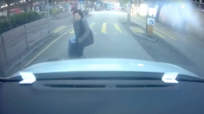 Woman throws herself at car bonnet