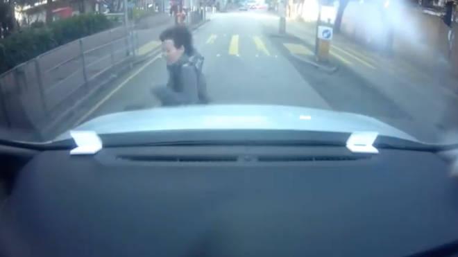 Woman throws herself onto bonnet