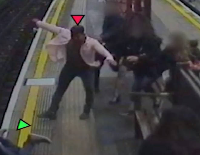 The shocking moment the passenger is shoved on to the tracks