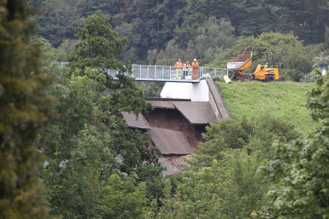 Engineers investigate damage to the wall of Toddbrook Reservoir near the village of Whaley Bridge, Cheshire, after it was damaged in heavy rainfall