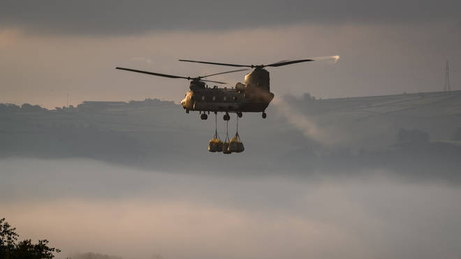 An RAF Chinook assists in the repair operation at Whaley Bridge after the dam began to collapse