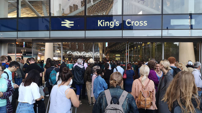 Passengers queueing outside Kings Cross station in London after power cut left services suspended for several hours
