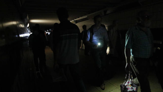 Commuters at Clapham Junction pull out their phones as major power outage plunges the station into darkness