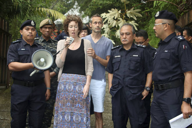 Meabh Quoirin, center left, the mother of a missing British girl Nora Anne Quoirin, speaks to police officers as father Sebastien Quoirin, center right, stands beside her, in Seremban, Negeri Sembilan, Malaysia