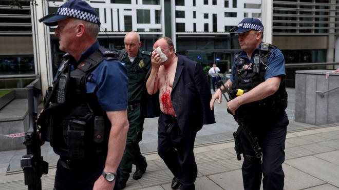 An injured man is led away from the Home Office