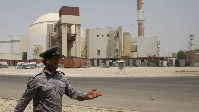 An Iranian security official directs media at the Bushehr nuclear power plant.