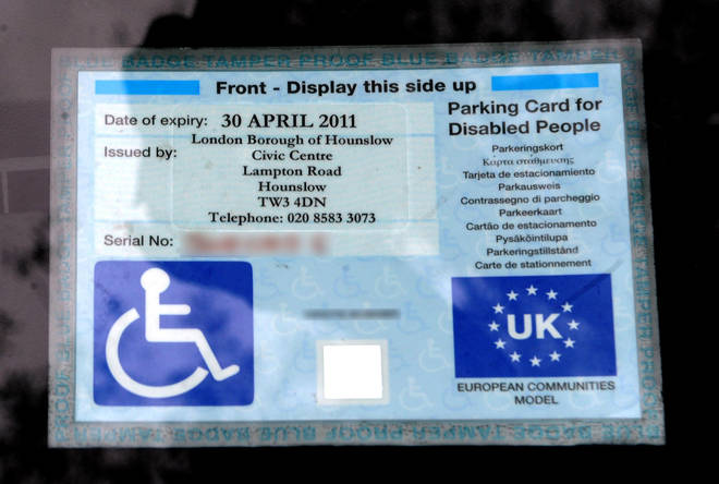 A disabled parking badge is displayed at a Sainsburys store in London.
