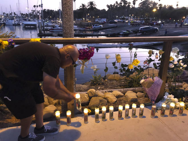 A man adds to the growing memorial for victims