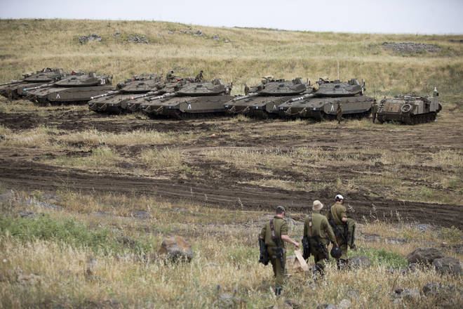 Israeli soldiers walk past tanks in the Israeli-controlled Golan Heights near the Syrian border.