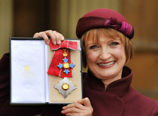Dame Tessa Jowell proudly holding her Dame Commander insignia.
