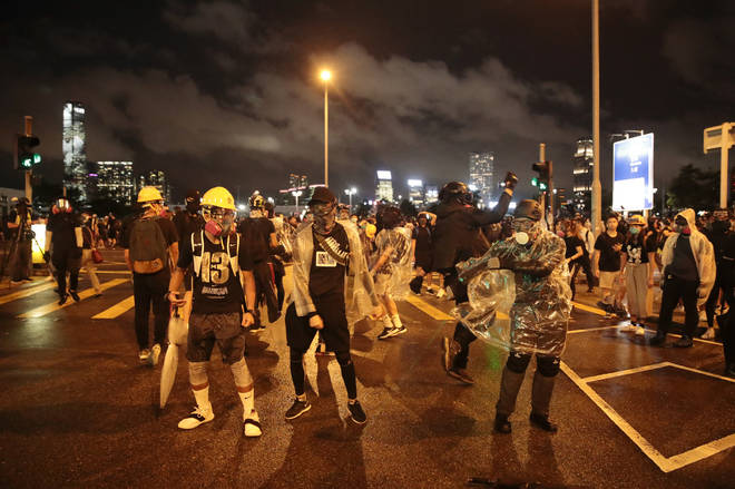 Protesters taunt police near the Chinese People's Liberation Army Forces Building in Hong Kong