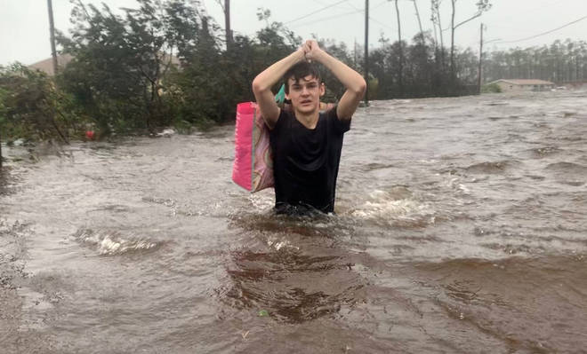 Matthew Aylen wades through waist deep water as he is rescued from his flooded home during Hurricane Dorian in Freeport, Bahamas.